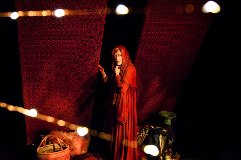 Holly Turner as Mary stands against a red and black backdrop.