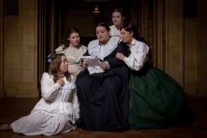 Five women gathered together reading a letter.