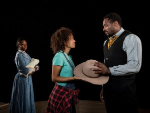 Jameela McNeil looks on as Kirsten Alter hands Jesse Lipscombe a cowboy hat.