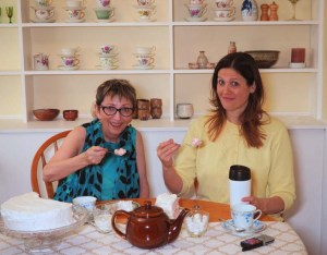 A mother and her grown daughter have tea and cake.