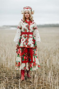 A woman in Ukranian clothes stands in a field.