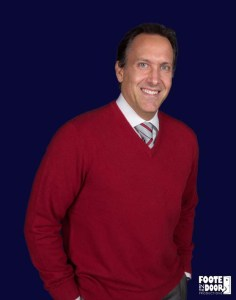 Man in red shirt standing with hands in pockets