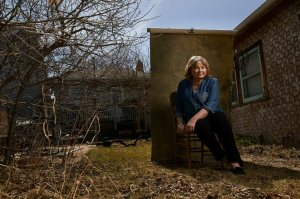 A woman poses for a portrait in a back yard.