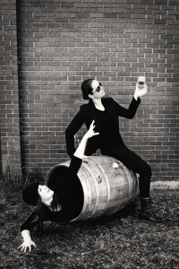 A woman sits on top of a whiskey barrel holding a glass of whiskey while another woman inside the barrel reaches for the glass
