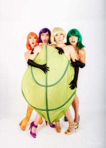Four naked women behind a large green leaf.