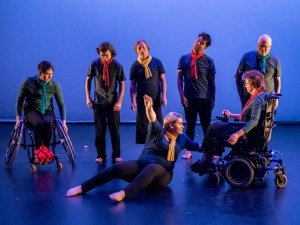 Dancers in scarves and black shirts stand off kilter while a dancer on the floor sits looking at a dancer in a wheelchair.
