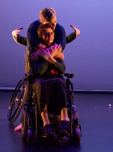 A dancer hugging another dancer from behind, while a third set of arms comes from behind.