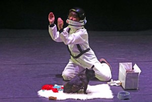 Astronaut kneels in front of a dog while gesturing.