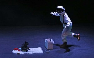 Astronaut walks as if in space while dog looks at her.