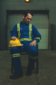A man in coveralls with a yellow hard hat sits on a chair in a warehouse looking down.