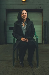 A woman in a winter coat sits in a warehouse and smiles at the camera.