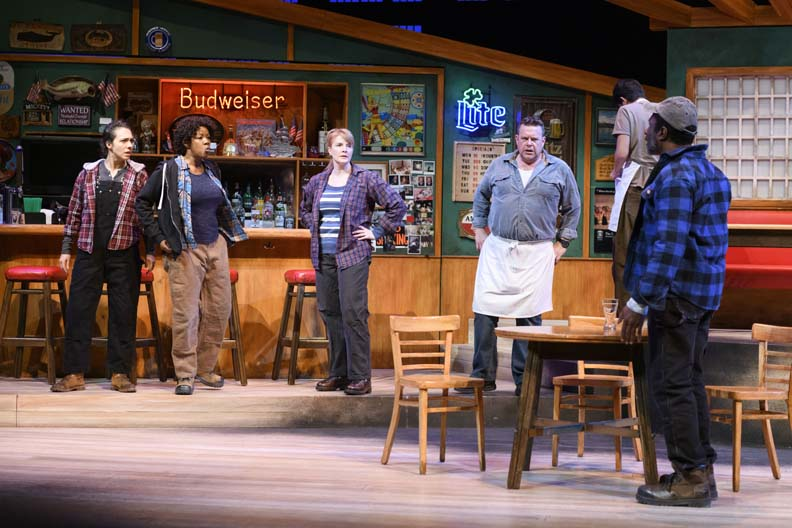 Five people stand in a bar confrontationally while a man cleans in the back.