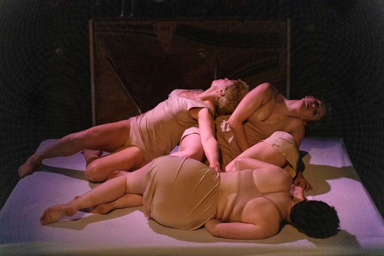 Four women laying on a bed draped over one another.