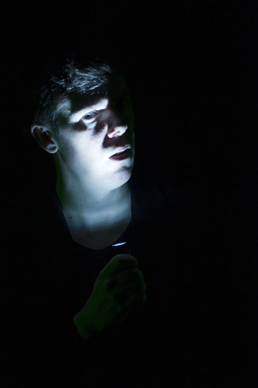 Damien Atkins looks concerned, holding a flashlight under his face, with the photo otherwise dark.