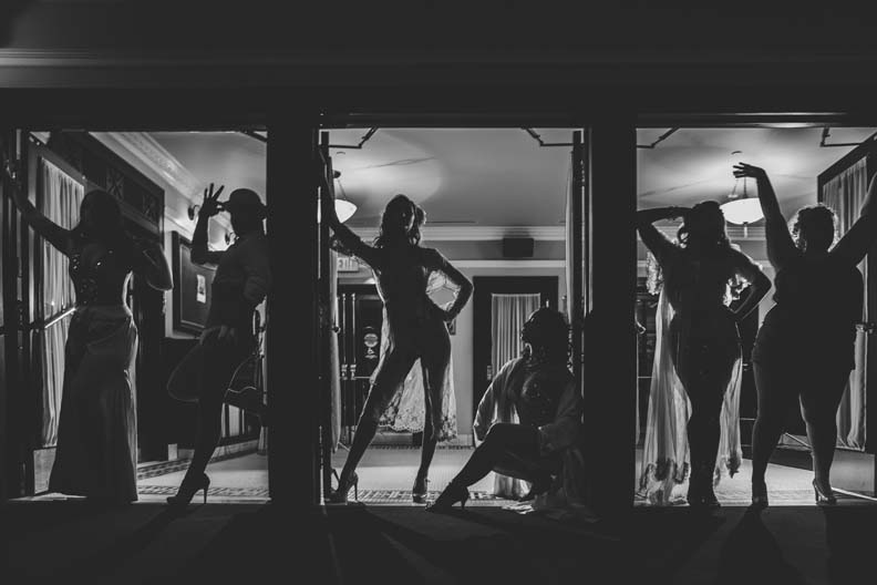 Back lit women standing in front of a window in various poses.