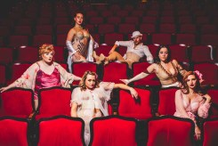 Five female and one male burlesque performers sitting in a theatre looking at the camera.